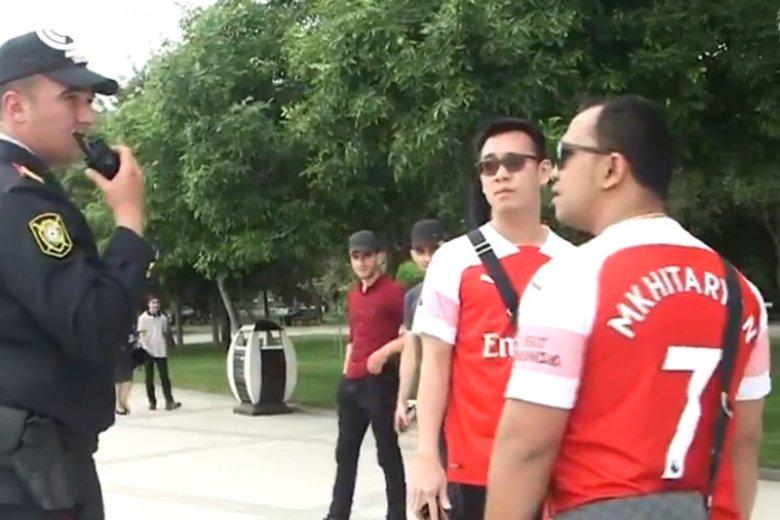 Azerscy policjanci zatrzymują kibiców Arsenalu w koszulkach z nazwiskiem Mchiturjan na plecach.