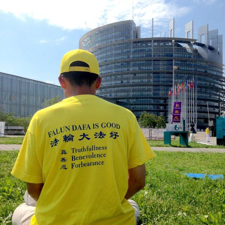 Uczeń Falun Gong (zaawansowana praktyka samodoskonalenia należącą do Szkoły Buddy) medytuje przed budynkiem Parlamentu Europejskiego, Strasburg, 2016