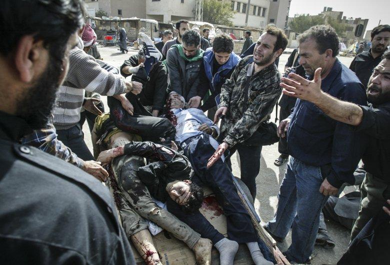 Irakijczycy zbierają ciała ofiar zamachu bombowego w czasie święta Ashura w Karbali.