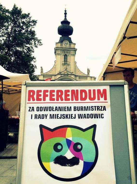 """Władze Wadowic od 20 lat opierają się demokracji. Głównie dzięki umiejętnemu """"rozgrywaniu"""" partii ogólnopolskich. Na plakacie symbol lokalnej polityki - Kocicho, czyli szef lokalnej PO."""