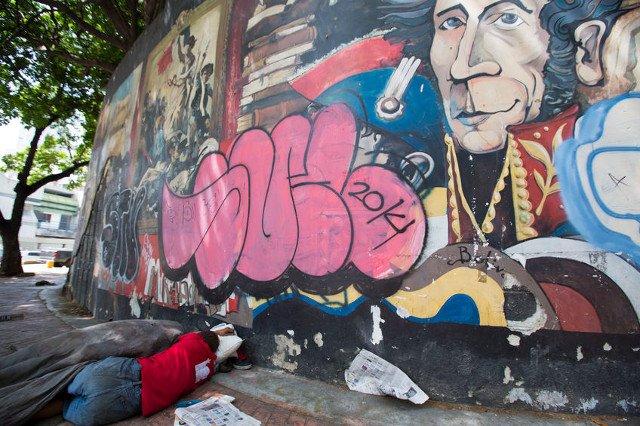Bezdomny śpi na ulicy w centrum Caracas pod graffiti przedstawiającym Simona Bolivara.