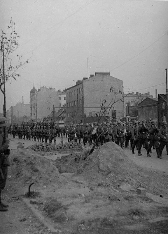1939 rok, niemieckie oddziały maszerują ulicą Wolską, w tle kamienica pod numerem 67.