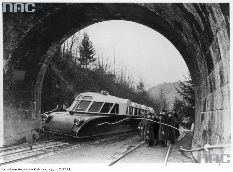 """Otwarcie odbudowanego tunelu kolejowego. Przejazd wagonu spalinowego """"lux-torpeda"""" przed grupą urzędników i oficerów."""
