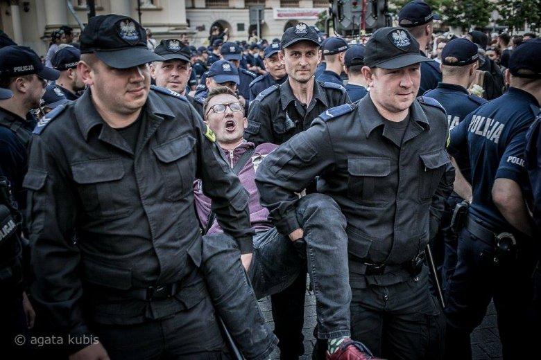 Młody mężczyzna wynoszony przez policjantów z blokady przy Krakowskim Przedmieściu w Warszawie.