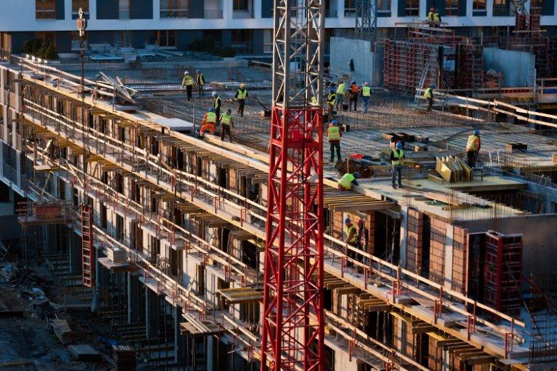 """Kraków, budowa mieszkań przy ul. Romanowicza, w miejscu dawnej fabryki. Raport """"Polski Rynek Nieruchomości"""" wskazuje, że w dużych miastach jest coraz mniej gruntów pod budowę mieszkań."""